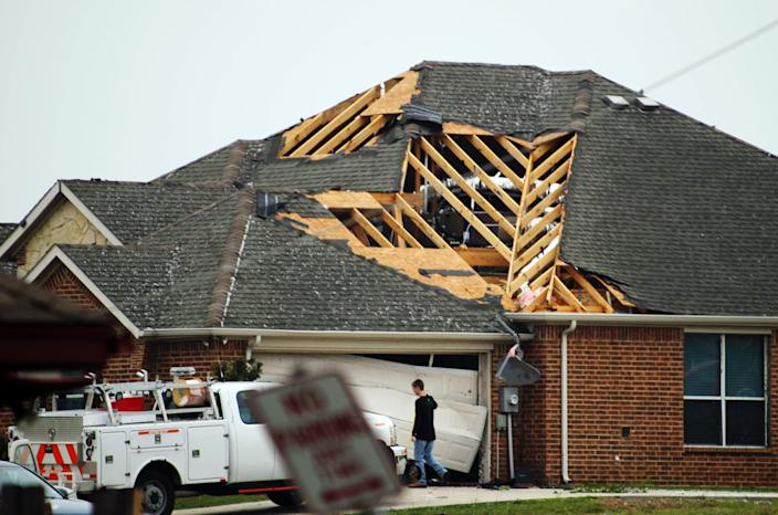 A man walks in front of a home damaged by Wednesday's tornado in Cleburne, Texas on Thursday, May 16, 2013. Ten tornadoes touched down in several small communities in Texas overnight, leaving at least six people dead, dozens injured and hundreds homeless. Emergency responders were still searching for missing people Thursday afternoon. (AP Photo/Ron Russek II)