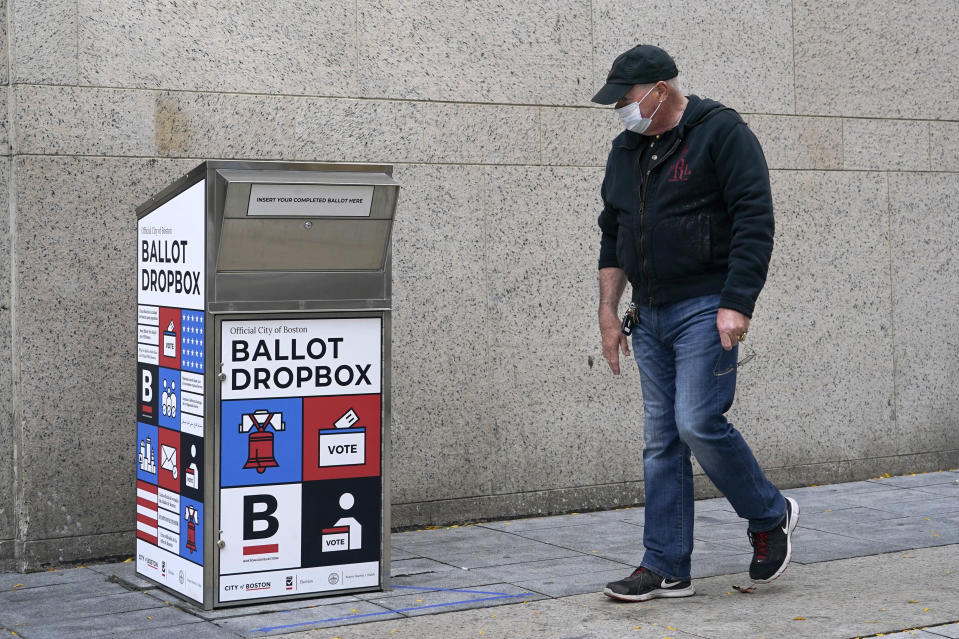 "A pedestrian walks by the ballot drop box outside the Boston Public Library, Monday, Oct. 26, 2020, in Boston. Massachusetts election officials say a fire was set in the ballot drop box Sunday, holding more than 120 ballots in what appears to have been a ""deliberate attack."" The FBI says it is investigating. (AP Photo/Elise Amendola)"