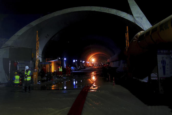Rescuers work on a flooded tunnel in Zhuhai city in south China's Guangdong province Thursday, July 15, 2021. Divers have been dispatched in the search for 14 workers missing since water flooded a tunnel under construction in southern China three days ago, authorities said Sunday, July 18, 2021. (Chinatopix via AP)
