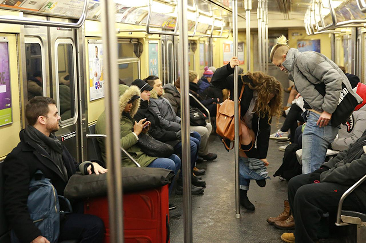 <p>Participants of the No Pants Subway Ride removes their pants as onlookers watch on the subway in New York City on Jan. 8. (Gordon Donovan/Yahoo News) </p>