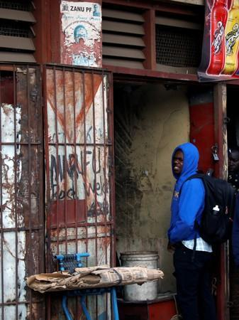 A man waits outside a groceries shop, near to a torn poster depicting late former Zimbabwe's President Robert Mugabe, in Mbare twonship, Harare