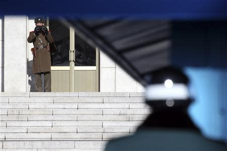 A North Korean soldier keeps watch as a South Korean soldier stands guard at the truce village of Panmunjom in the demilitarised zone separating the two Koreas, north of Seoul February 6, 2014. REUTERS/Han Jae-ho/News1