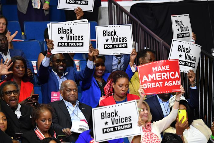 """Herman Cain (C,L) and supporters of US President Donald Trump """"Black Voices"""" listen to him speak during a campaign rally at the BOK Center on June 20, 2020 in Tulsa, Oklahoma. (Nicholas Kamm/AFP via Getty Images)"""