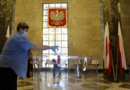 A resident, wearing face mask and protective gloves, casts a vote during presidential election in Warsaw, Poland, Sunday, June 28, 2020. The election will test the popularity of incumbent President Andrzej Duda who is seeking a second term and of the conservative ruling party that backs him. (AP Photo/Petr David Josek)