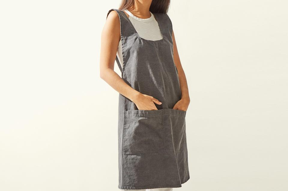 """This cotton apron has a washed-denim feel that makes it one of the sturdiest in the bunch. It's machine washable and doesn't require any ironing—just pull it out of the dryer and throw it on before cooking, gardening, or painting. It's fully equipped with two large pockets for keeping all of your <a href=""""https://www.bonappetit.com/story/kunz-spoon?mbid=synd_yahoo_rss"""" rel=""""nofollow noopener"""" target=""""_blank"""" data-ylk=""""slk:Kunz spoon"""" class=""""link rapid-noclick-resp"""">Kunz spoon</a> and <a href=""""https://www.bonappetit.com/story/best-mini-spatula-gir?mbid=synd_yahoo_rss"""" rel=""""nofollow noopener"""" target=""""_blank"""" data-ylk=""""slk:mini spatula"""" class=""""link rapid-noclick-resp"""">mini spatula</a> within reach at all times. Bonus: At under $20, it's also the most affordable of the lot. $20, Cost Plus World Market. <a href=""""https://www.worldmarket.com/product/gray+washed+cotton+smock.do"""" rel=""""nofollow noopener"""" target=""""_blank"""" data-ylk=""""slk:Get it now!"""" class=""""link rapid-noclick-resp"""">Get it now!</a>"""