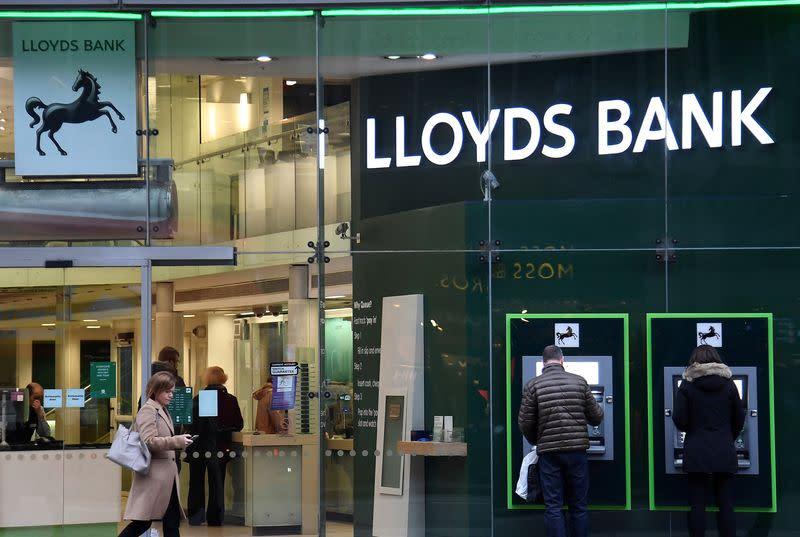 FILE PHOTO: Customers use ATMs at a branch of Lloyds Bank in London