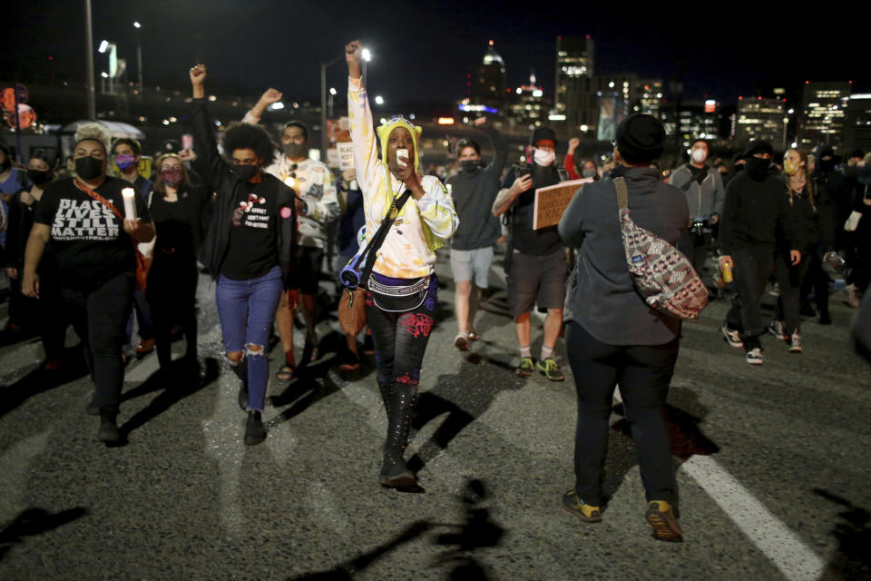 A group marches along the Hawthorne Bridge after meeting at Salmon Street Springs and listening to several Black and Indigenous speakers talk, Friday, April 16, 2021, in Portland, Ore. Police in Portland, said Saturday they arrested several people after declaring a riot Friday night when protesters smashed windows, burglarized businesses and set multiple fires during demonstrations that started after police fatally shot a man while responding to reports of a person with a gun. (Dave Killen/The Oregonian via AP)