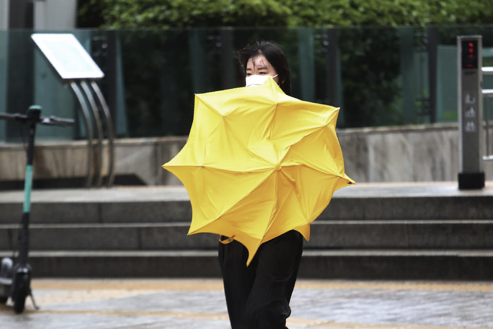 A woman holds an umbrella against the strong wind and rain caused by Typhoon Bavi in Seoul, South Korea, Thursday, Aug. 27, 2020. Typhoon Bavi that grazed South Korea and caused some damage has made landfall in North Korea early Thursday. South Korean authorities said there were no immediate reports of casualties, and North Korea has not reported any damages. (AP Photo/Ahn Young-joon)