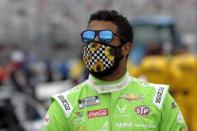 FILE - In this Sunday, Aug. 2, 2020, file photo, driver Bubba Wallace waits for the start of a NASCAR Cup Series auto race at the New Hampshire Motor Speedway in Loudon, N.H. The pandemic only accelerated the inevitable: The driver market bubble, pushed to its limit with multi-million dollar salaries for nearly two decades, is about to burst. A major reset has arrived and team owners have all the power. They can pick and choose between drivers who bring sponsorship dollars (Bubba Wallace) or drivers who have won races (Erik Jones). (AP Photo/Charles Krupa, File)