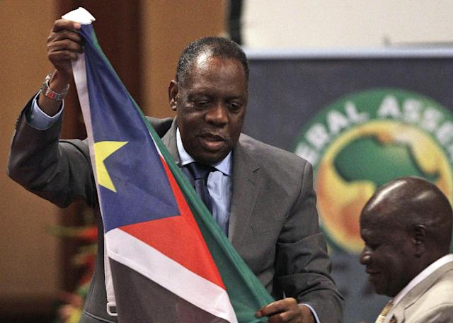 Confederation of African Football (CAF) president Issa Hayatou, left, receives South Sudan's national flag from its federation president Oliver Benjamin, right, during the Confederation of African Football General Assembly in Libreville, Gabon, Friday Feb. 10, 2012. South Sudan was admitted as a member of the Confederation of African Football on Friday, becoming the world's newest footballing nation. (AP Photo/Themba Hadebe)
