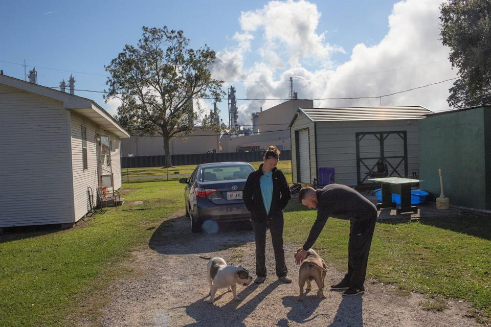 A couple plays with their dogs at a Louisiana home with a refinery in the background.