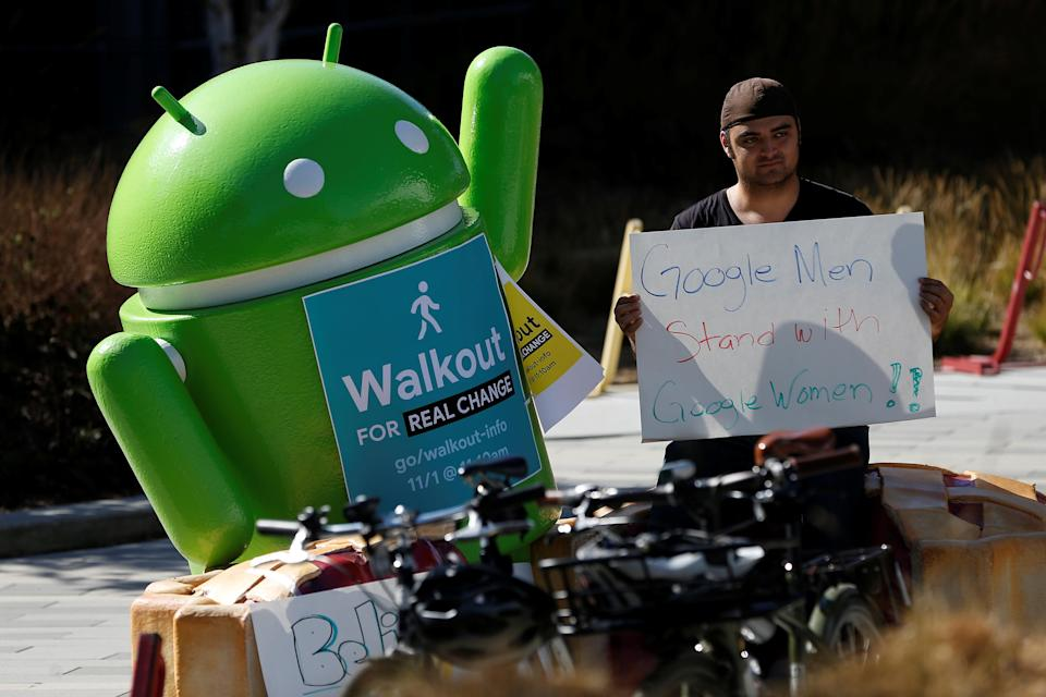 "A Google employee holds a sign next to an Android mascot during a ""women's walkout"" at their Googleplex offices. November 1, 2018. REUTERS/Stephen Lam"