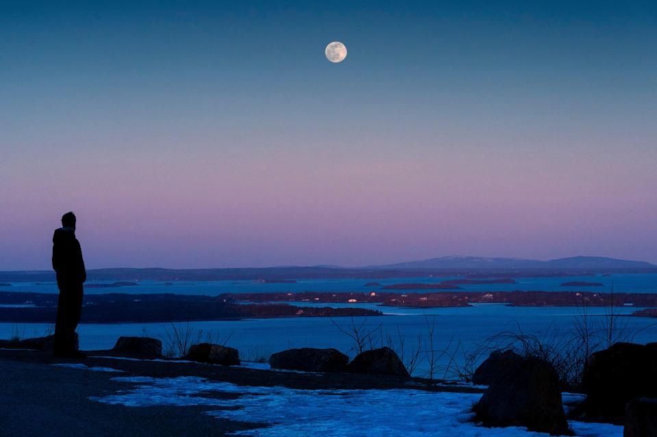 """Shawn Griffith, of South Port, Maine, watches the """"snow moon"""" rise in clear skies over Penobscot BayAP"""