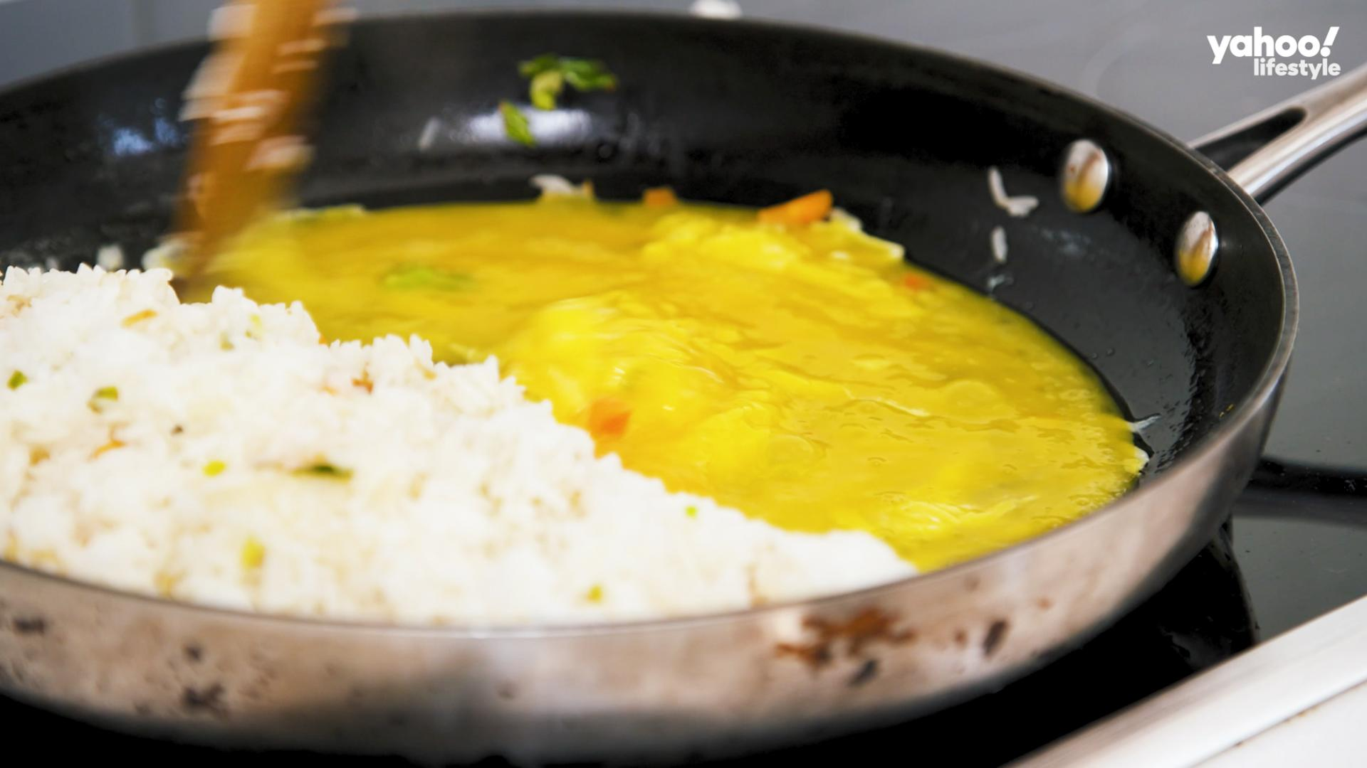 Push rice to one side of pan, pour in eggs, stirring constantly until they are just cooked.