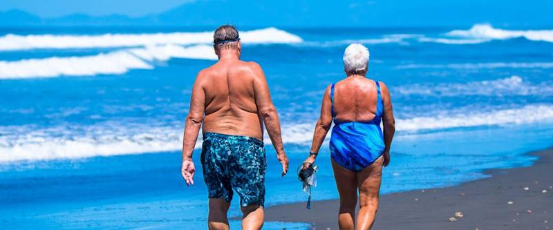 Older people walking along the beach. Costa Rica, tourist paradise
