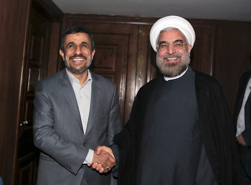FILE - In this Tuesday, June 18, 2013 file photo provided by the official website of the office of the Iranian presidency, outgoing Iranian President Mahmoud Ahmadinejad, left, shakes hands with President-elect Hasan Rouhani during a meeting at Rouhani's office, in Tehran, Iran. As Rouhani prepares to address the United Nations for the first time on Tuesday, he has already made a deep impression on world leaders with his markedly milder tone and apparent willingness to reopen negotiations with the West on Iran's disputed nuclear program. In contrast, Ahmadinejad was jeered and pilloried during his eight visits to U.N. headquarters in New York. (AP Photo/Presidency Office, Ebrahim Seyyedi, File)