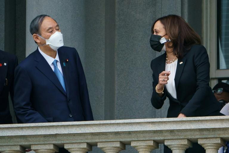 US Vice President Kamala Harris greets Japanese Prime Minister Yoshihide Suga on a balcony ahead of a meeting