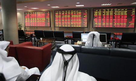 Investors monitor market activity at the Qatar Exchange in Doha
