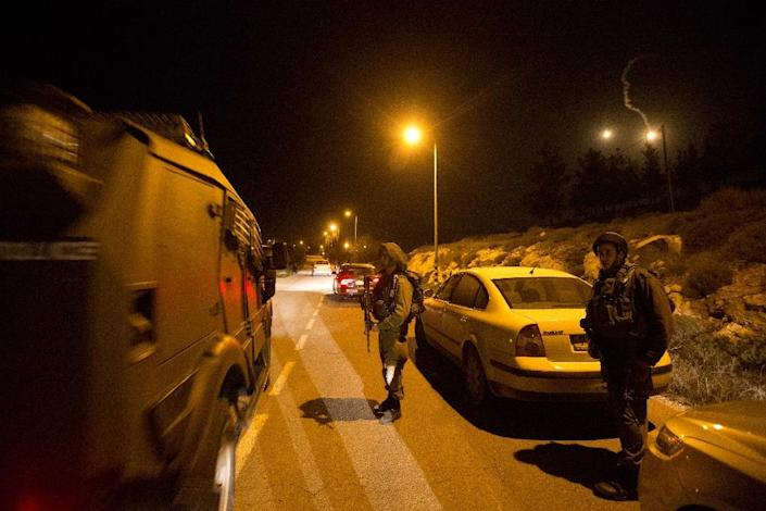 Israeli soldiers block the entrance of the Otniel settlement in the southern West Bank after a suspected Palestinian attacker stabbed to death Dafna Meir, a 40-year-old mother, at her home on January 17, 2016 (AFP Photo/Menahem Kahana)