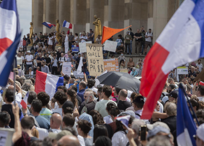Protesters attend a demonstration in Paris, France, Saturday July 24, 2021, against the COVID-19 pass which grants vaccinated individuals greater ease of access to venues. (AP Photo/Rafael Yaghobzadeh)