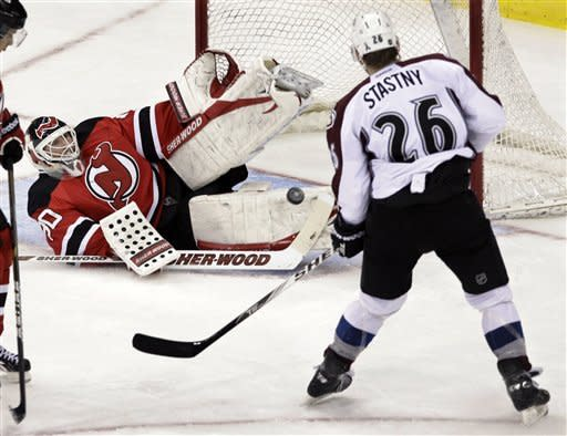 Colorado Avalanche's Paul Stastny (26) watches a shot as New Jersey Devils goalie Martin Brodeur falls to make a save during the second period of an NHL hockey game in Newark, N.J., Thursday, March 15, 2012. (AP Photo/Mel Evans)