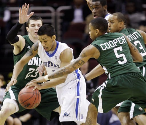 Buffalo's Tony Watson, center, drives between Ohio's Ivo Baltic, rear, and D.J. Cooper in the first half of an NCAA college basketball game in the Mid-American Conference tournament semifinals, Friday, March 9, 2012, in Cleveland. (AP Photo/Tony Dejak)
