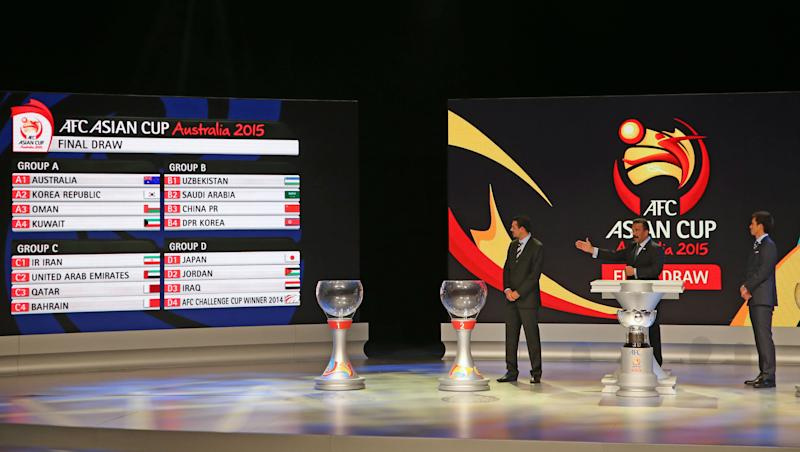AFC General Secretary Dato' Alex Soosay, center, and Japan's Takashi Fukunishi, right, and Iraq's Younis Mahmoud stand on stage following the Asian Football Confederation draw for the 2015 Asian Cup at the Sydney Opera House ground in Sydney, Wednesday, March 26, 2014. Australia hosts the tournament that will be played in Jan. 2015. (AP Photo/Rick Rycroft)