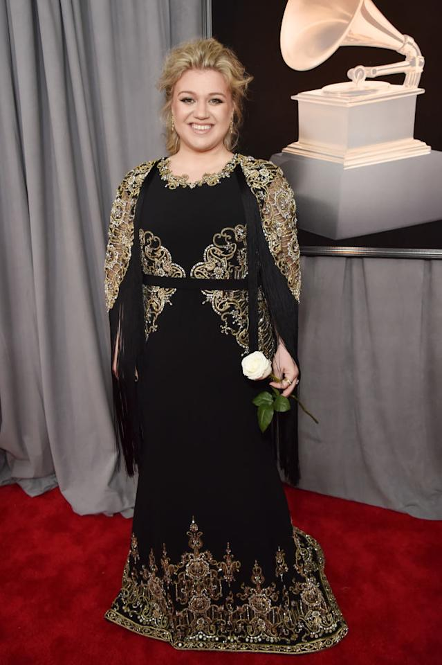 <p>Kelly Clarkson donned a romantic, lacy black-and-gold gown — the same colors she chose for the Golden Globes earlier this month — on the red carpet for the 60th Annual Grammy Awards. Instead of wearing a white rose, she chose to carry the flower. (Photo: John Shearer/Getty Images) </p>
