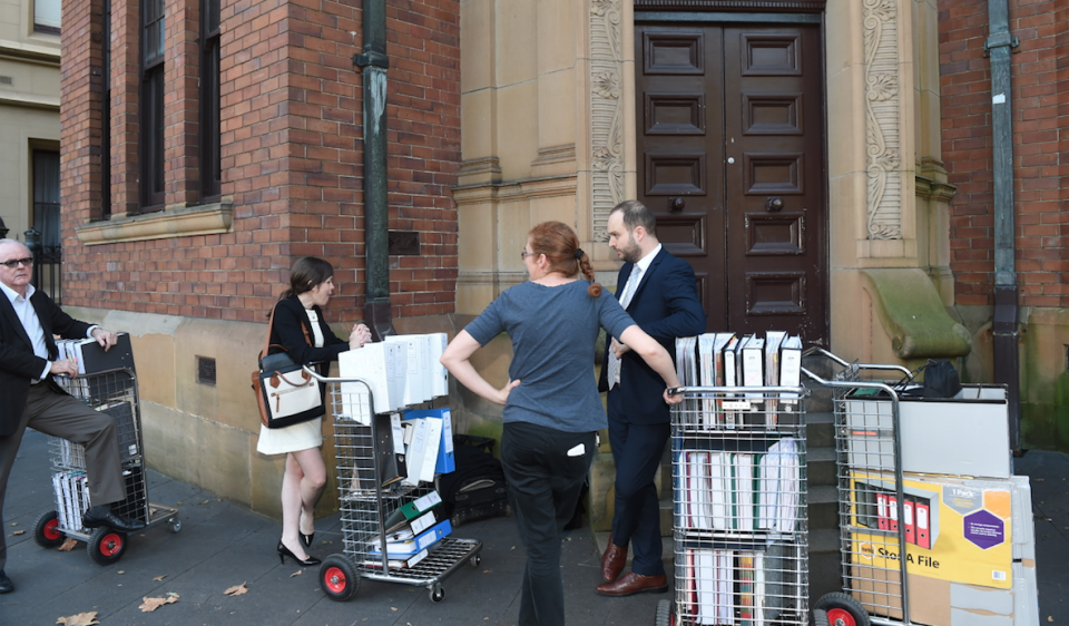 Lawyers and associates wait with trolleys of documents for the Oliver Curtis trial. Photo: AAP