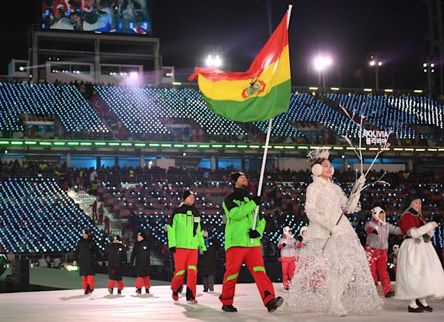<p>Flag bearer Simon Breitfuss Kammerlander of Bolivia leads out his country, who all wear lime green ski jackets and red pants during the opening ceremony of the 2018 PyeongChang Games. (Photo: Quinn Rooney/Getty Images) </p>