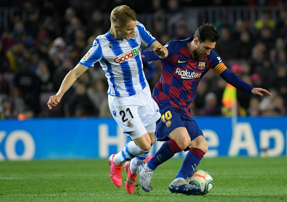Real Sociedad's Norwegian midfielder Martin Odegaard (L) challenges Barcelona's Argentine forward Lionel Messi during the Spanish league football match between FC Barcelona and Real Sociedad at the Camp Nou stadium in Barcelona on March 7, 2020. (Photo by LLUIS GENE / AFP) (Photo by LLUIS GENE/AFP via Getty Images)