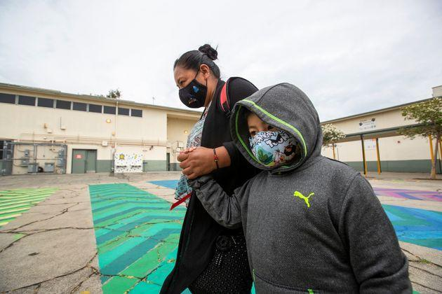 First grade student Daniel Cano, 5, and his mom, Sonia Cano, walk past COVID-19 safety precaution signs at Euclid Avenue Elementary School Monday, July 26, 2021 in Los Angeles. (Photo: Allen J. Schaben via Getty Images)