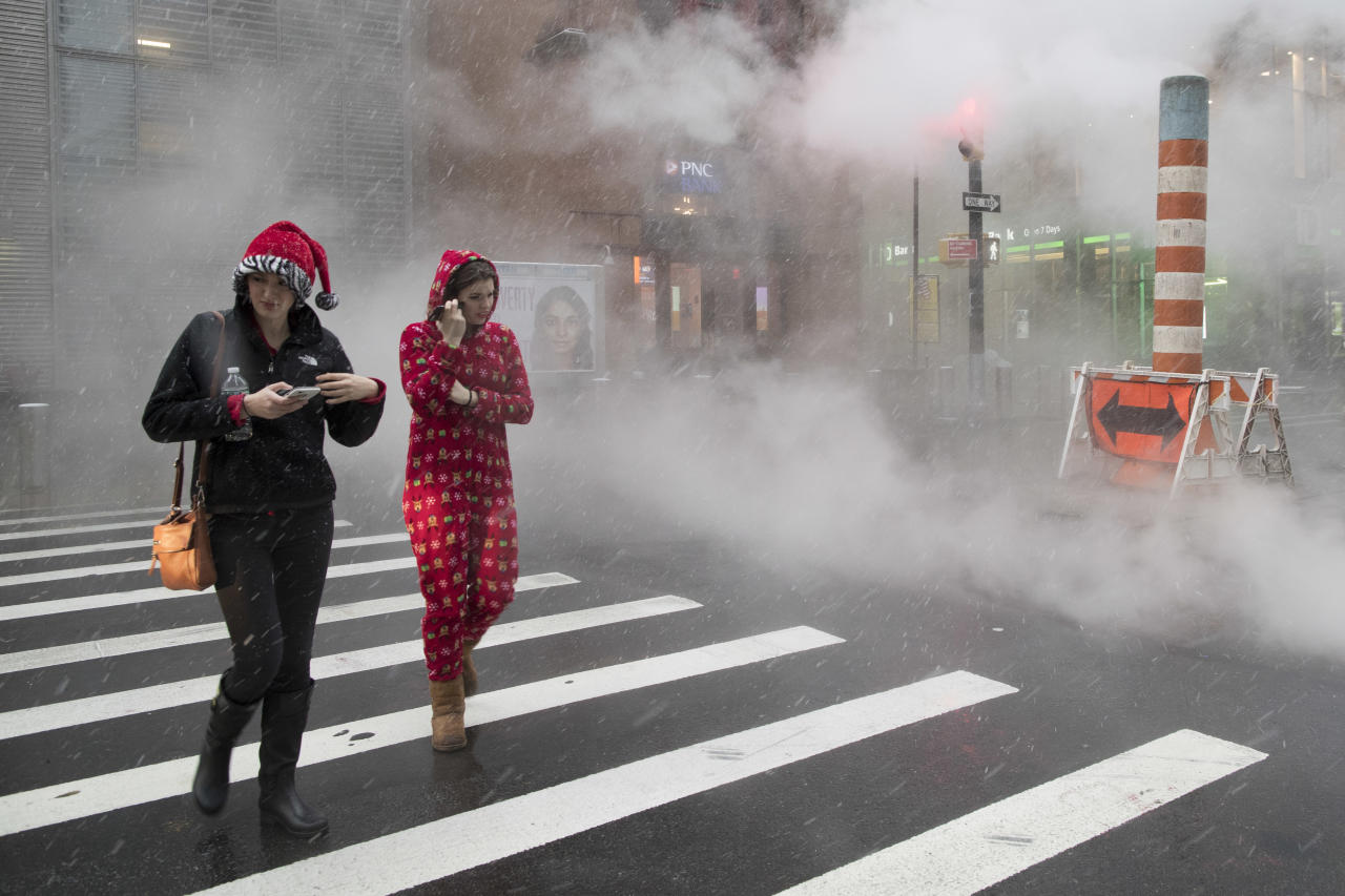 <p>Snow falls on a couple of Santa Con revelers as they bar hop in lower Manhattan, Saturday, Dec. 9, 2017, in New York. (Photo: Mary Altaffer/AP) </p>