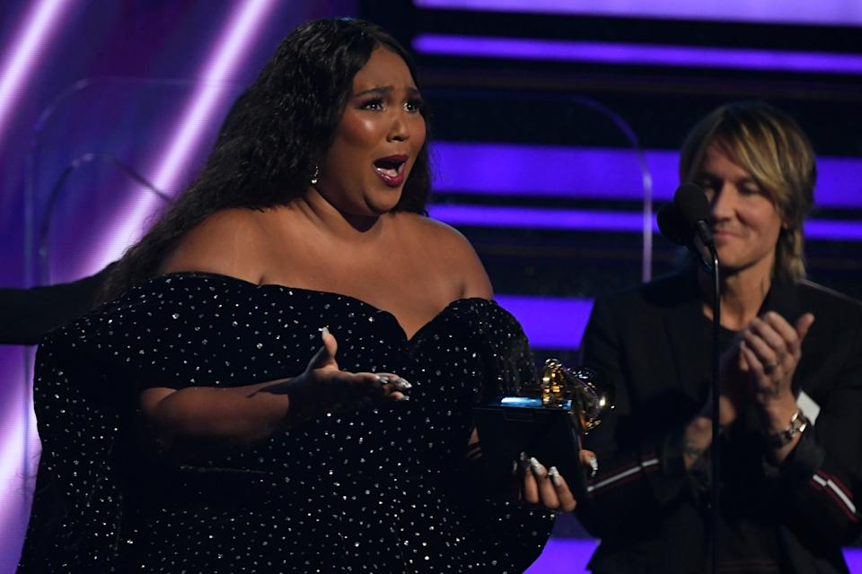 An emotional Lizzo accepts the award for best pop solo performance during the 62nd annual Grammy Awards.