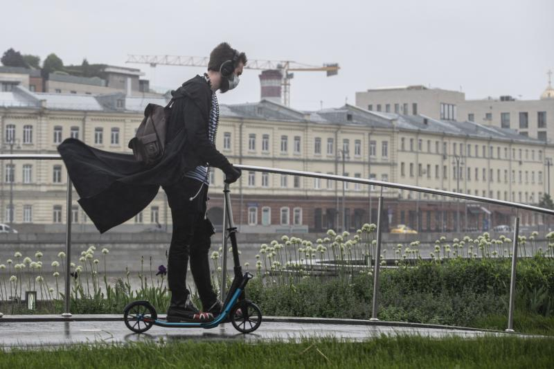A man wearing a face mask and gloves to protect against coronavirus, rides a scooter in the rain along a boulevard in Moscow, Russia, on Tuesday, June 2, 2020. The authorities in Moscow allowed the city residents limited walks in the parks starting Monday for the first time since a tight lockdown was introduced in late March. (AP Photo/Alexander Zemlianichenko Jr)