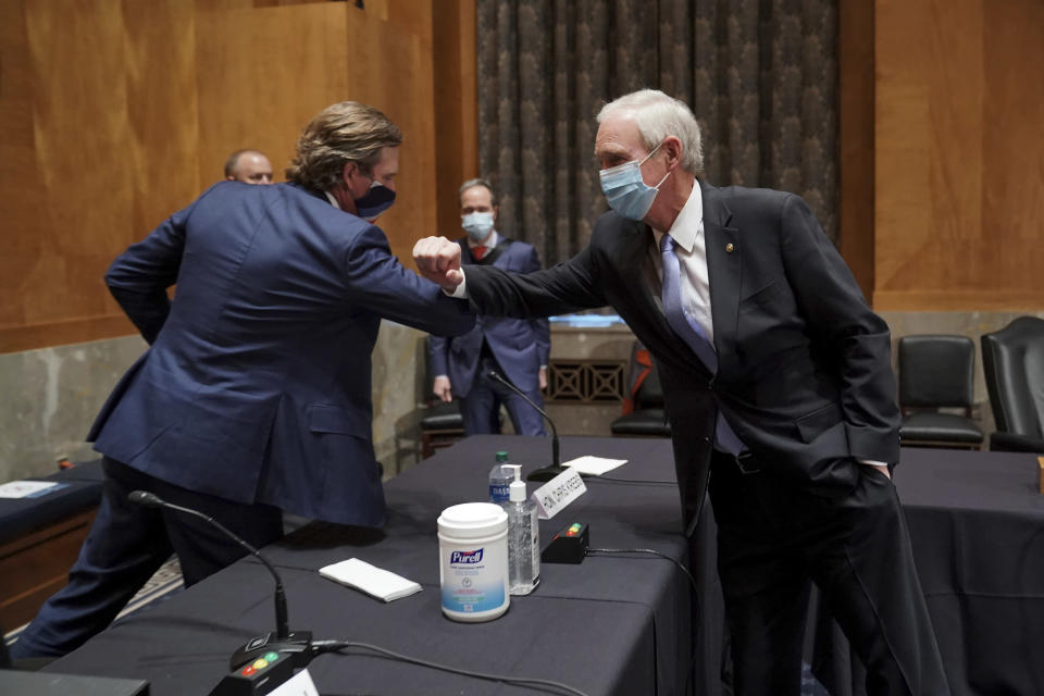 Christopher Krebs, former director of the Cybersecurity and Infrastructure Security Agency, elbow bumps Senate Homeland Security and Governmental Affairs Committee Chairman Ron Johnson, R-Wis., after a hearing to discuss election security and the 2020 election process on Wednesday, Dec. 16, 2020, on Capitol Hill in Washington. (Greg Nash/Pool via AP)