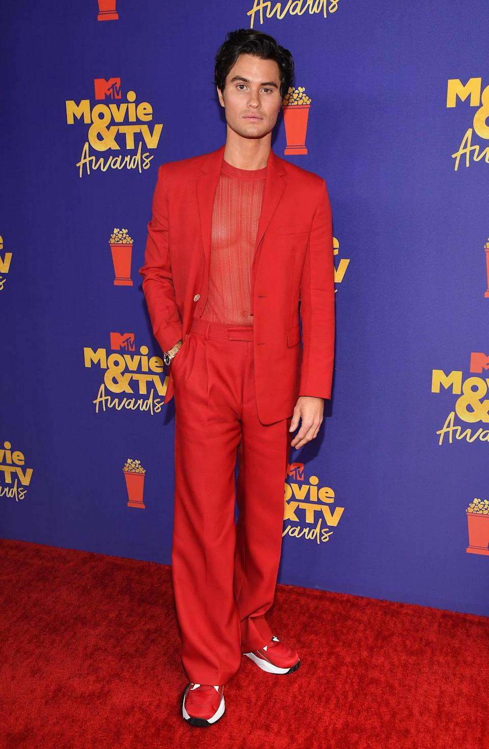 """<p>Wearing a <a href=""""https://www.popsugar.com/fashion/chase-stokes-outfit-mtv-movie-tv-awards-2021-48326469"""" class=""""link rapid-noclick-resp"""" rel=""""nofollow noopener"""" target=""""_blank"""" data-ylk=""""slk:Fendi look"""">Fendi look</a> with an Omega timepiece.</p>"""