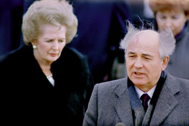 Then-Soviet Leader Mikhail Gorbachev, with his hair swept by the wind, delivers a farewell speech before leaving Great Britain at the end of an official visit, as then-British Prime Minister Margaret Thatcher looks on at London airport, April 7, 1989 (AFP Photo/Patrick Anderson)