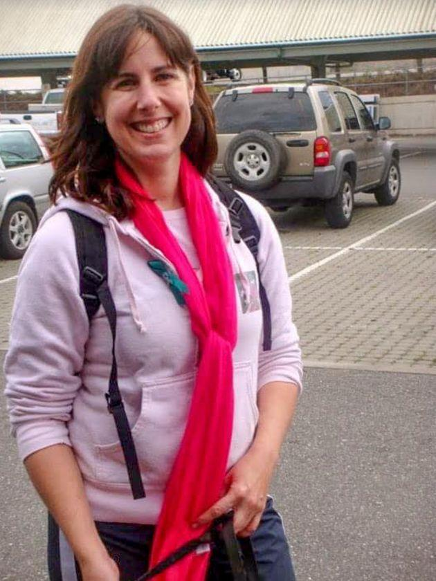 The author learned the symptoms of ovarian cancer a decade before her own diagnosis. In this 2010 photo taken at a Cancer Walk, she's wearing pink for breastcancer awareness and a small teal ribbon signifying ovarian cancer. (Photo: Courtesy of Kari Neumeyer)