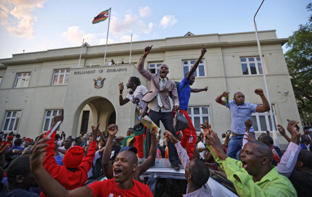 <p>Zimbabweans celebrate outside the parliament building immediately after hearing the news that President Robert Mugabe had resigned, in downtown Harare, Zimbabwe Tuesday, Nov. 21, 2017. (Photo: Ben Curtis/AP) </p>