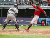 Cleveland Indians' Eddie Rosario, right, scores on a single by Franmil Reyes as Detroit Tigers' Wilson Ramos, left, waits for the ball during the eighth inning of a baseball game in Cleveland, Sunday, April 11, 2021. (AP Photo/Phil Long)