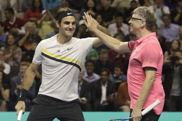Roger Federer, of Switzerland, left, celebrates with partner Bill Gates as they play an exhibition tennis match against Jack Sock and Savannah Guthrie in San Jose, Calif., Monday, March 5, 2018. (AP Photo/Jeff Chiu)