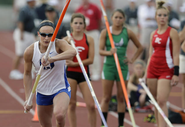 Emory Rains High School's Charlotte Brown, left, competes in the Girls 3A pole vault at the UIL State Track & Field meet, Friday, May 9, 2014, in Austin, Texas. Brown, a pole vaulter who happens to be legally blind, starts on the clap from her coach and counts her steps on her approach. (AP Photo/Eric Gay)