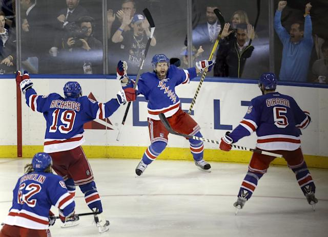New York Rangers' Martin St. Louis, center, celebrates his game-winning goal during overtime in Game 4 of the NHL hockey Stanley Cup playoffs Eastern Conference finals against the Montreal Canadiens, Sunday, May 25, 2014, in New York. The Rangers defeated the Canadiens in overtime 3-2. (AP Photo/Seth Wenig)