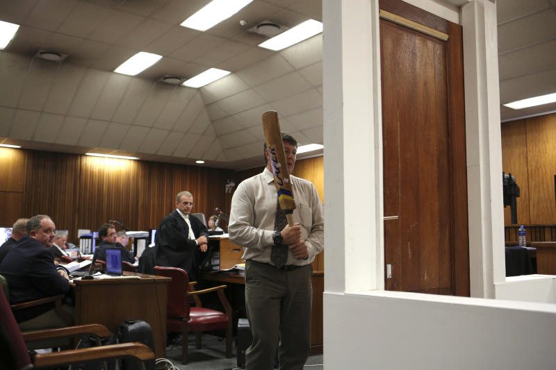 Forensic investigator Johannes Vermeulen, with a cricket bat in hand, demonstrates on a mock-up toilet and door details of how the door could have been broken down, during the trial of Oscar Pistorius in court during the second week of his trial in Pretoria, South Africa, Wednesday, March 12, 2014. Pistorius is charged with the shooting death of his girlfriend Reeva Steenkamp on Valentine's Day in 2013. At center back is prosecutor Gerrie Nel. (AP Photo/Alexander Joe, Pool)