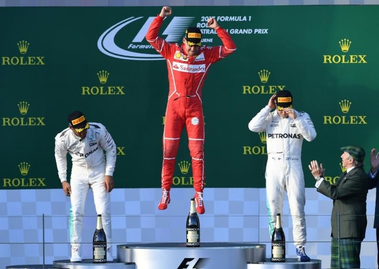 Ferrari's Sebastian Vettel (C) celebrates on the podium beside second-placed Mercedes' Lewis Hamilton (L) and third-placed Mercedes' Valtteri Bottas at the Australian Grand Prix in Melbourne