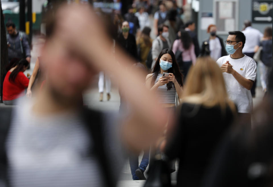 Shoppers wearing protective face masks walk along Oxford Street in London, Tuesday, July 14, 2020.Britain's government is demanding people wear face coverings in shops as it has sought to clarify its message after weeks of prevarication amid the COVID-19 pandemic. (AP Photo/Frank Augstein)