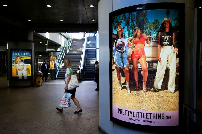 FILE PHOTO: A shopper walks pass advertising billboards for Boohoo and for 'Pretty Little Things', a Boohoo brand, at Canary Wharf DLR station in central London