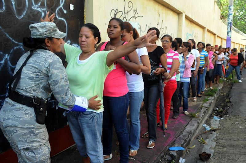 A Dominican Republic soldier frisks a voter waiting in the women's line to cast their ballots during the presidential election in Santo Domingo, Dominican Republic, Sunday May 20, 2012. (AP Photo/Manuel Diaz)
