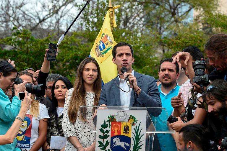 """The head of Venezuelas National Assembly and the countrys self-proclaimed """"acting president"""" Juan Guaido (C), accompanied by his wife Fabiana Rosales (C-L), gestures before a crowd of opposition supporters during a rally in Caracas, on January 26, 2019. (Photo by Federico PARRA / AFP)"""